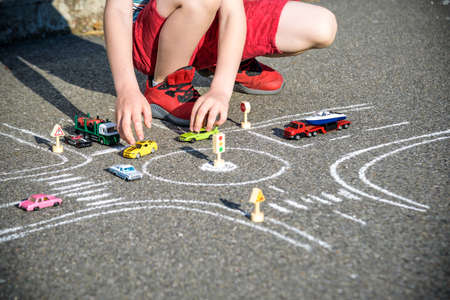 Funny kid boy having fun with picture drawing traffic car with chalks. Creative leisure for children outdoors in summer. Difficult traffic rules concept. Close up