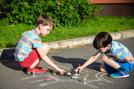 Two brothers sibling kid boy having fun with picture drawing traffic car with chalks. Creative leisure for children outdoors in summer. Difficult traffic rules education friendship concept. 写真素材