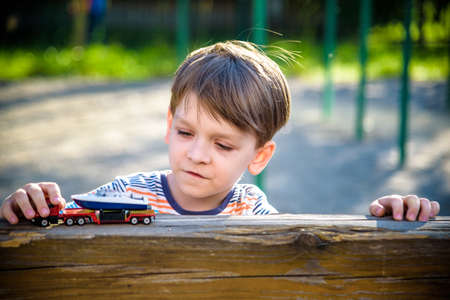Boy plays with toy cars. Kid playing on the playground alone. Child's daytime fun.