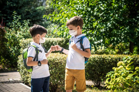 children greeting. Kids wearing mask and backpacks protect and safety coronavirus for back to school. Bou and girl going school after pandemic over. Archivio Fotografico