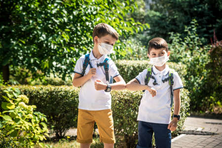 children greeting. Kids wearing mask and backpacks protect and safety coronavirus for back to school. Bou and girl going school after pandemic over.