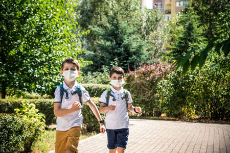 Happy schoolchildren with face masks run from the joy of returning to school during the Covid-19 quarantine.