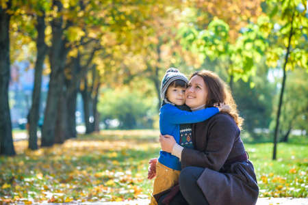 Mother and baby play in autumn park. Parent and child walk in the forest on a sunny fall day. Children playing outdoors with yellow maple leaf. Toddler boy play with golden leaves. Mom hugging kid. Stock fotó