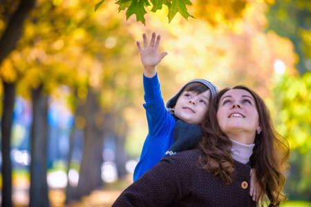 Cute, happy, boy smiling and hugging with his mom among yellow leaves. Little child having fun with mother in autumn park. Concept of friendship between son and parents, happy family.