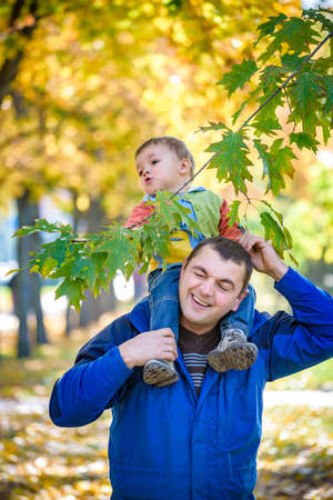 family, childhood and fatherhood concept. happy father carrying son with maple leaves over autumn park background. Autumn mood. Positive emotions. Lifestyle