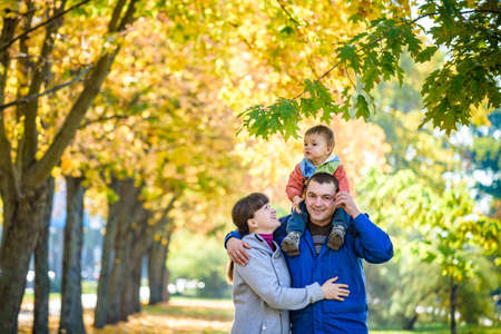 Family of three walks in the autumn park holding hands. happy father carrying son with maple leaves. Mother embrace her cute boy child. Happy family leisure together concept.