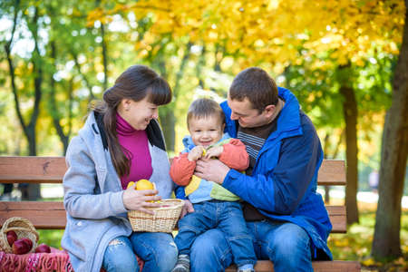 happy family enjoying autumn picnic. Father mother and son sit on bench with apples basket. Happy family leisure together concept.