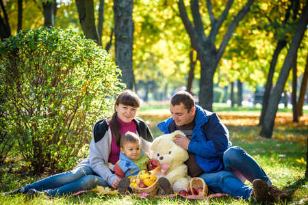 happy family enjoying autumn picnic. Father mother and son sit on field with apples basket teddy bear and reading book. Happy family leisure together concept.