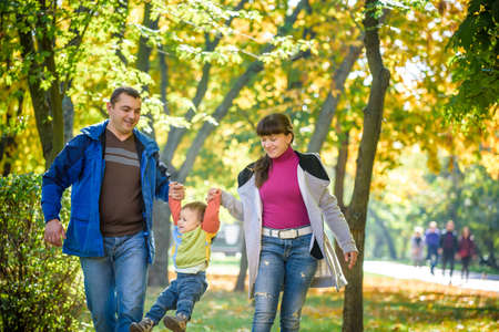Beautiful young family on a walk in autumn forest on maple yellow trees background. Father and mother hold son on hands. Happy family leisure together concept.