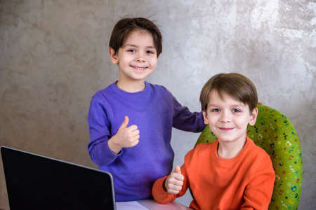 Happy overjoyed boy with his friend screaming excitedly, keeping fists pumped while playing video games on laptop pc, cheering after he won, his little brother smiling joyfully in background Stok Fotoğraf