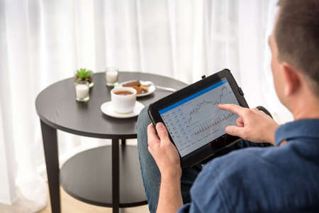 Man trading digital currencies online while relaxing by the cup of coffee in expencive hotel room. Imagens