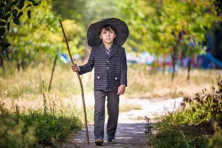 Toddler boy in pointed hat playing with magic wand outdoors. Little wizard. Halloween concept.