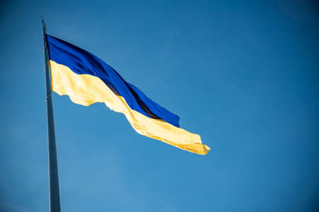 Ukrainian flag on top of hill. clear blue sky with clouds.