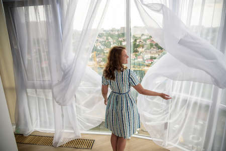 Rear view of a young joyful woman wearing fashion dress and holding the curtains open to look out of large light window at home, turning to look and smile at camera, interior.