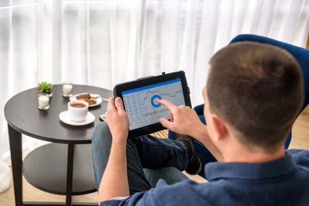 Man trading digital currencies online while relaxing by the cup of coffee in expencive hotel room. Banco de Imagens