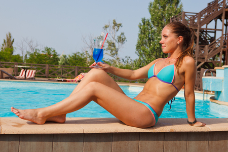 sunbath: girl with cocktail near pool