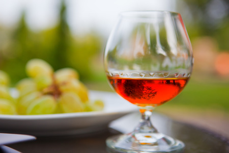 old desk: Cognac in a glass with grapes Stock Photo