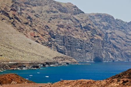 steep: fishboats in ocean near rocks Stock Photo