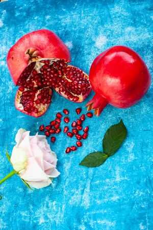 Garnet grains on blue background with rose flower