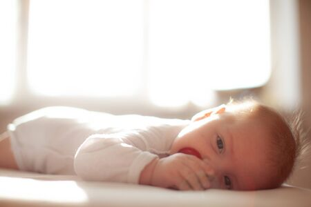 infant laying with pacifier on bed in lights of a sun Standard-Bild