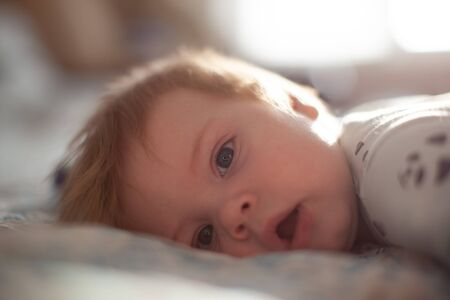 infant in bed lying playing