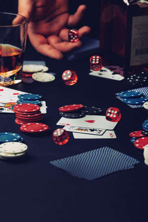 casino with hand throwing dice on cards with whiskey