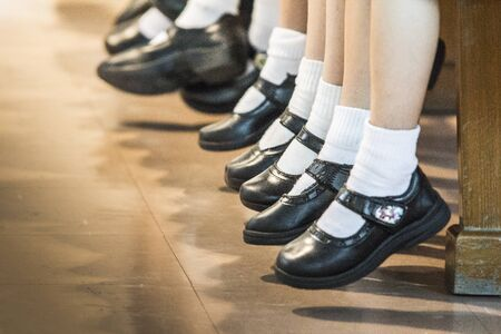 zapatos escolares: los zapatos del uniforme escolar de Tailandia de niños sentados en una fila.