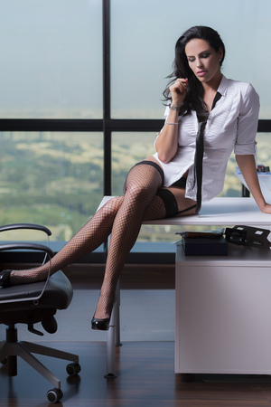 Sexy businesswoman sitting on desk in underwear with glasses, white shirt and black neck tie