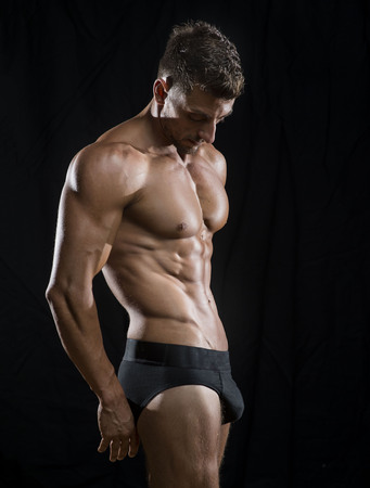 Mature athlete posing in underwear with dramatic lighting black background