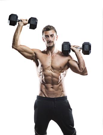 mature athlete posing with dumbells, smiling, dramatic lighting on white background Stock Photo