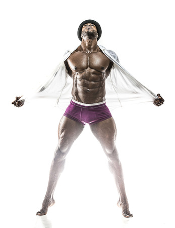 Handsome muscular Arabic man removing a wet white shirt showing abs and black underwear, bowler hat with oiled body Zdjęcie Seryjne