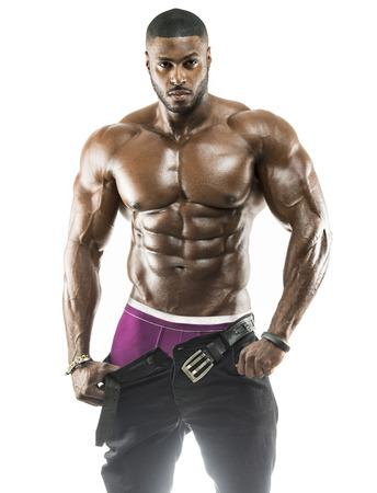 Apuesto hombre negro árabe musculoso quitándose los pantalones mostrando abdominales y ropa interior negra con cuerpo engrasado