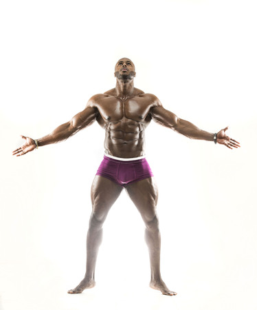 Handsome muscular Arabic man showing abs, arms open looking up with oiled body in dramatic pose showing underwear