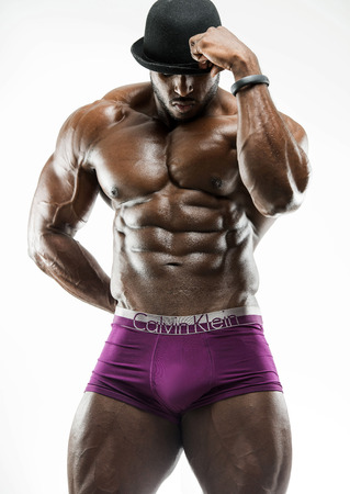 Handsome muscular Arabic Black man showing abs, arms open looking down with oiled body in  pose showing six pack and underwear wearing a black  hat
