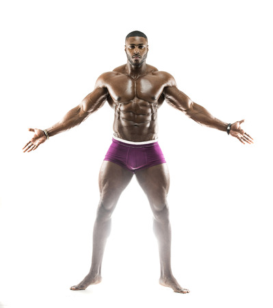 Handsome muscular Arabic Black man showing abs, arms open looking up with oiled body in dramatic pose showing underwear wearing a black  hat Imagens