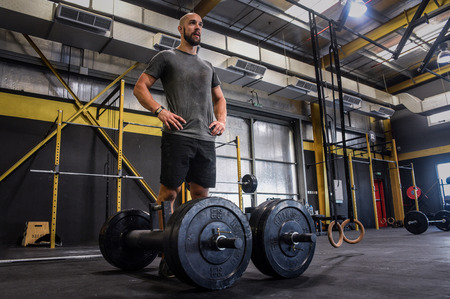 Strong crossfit athletic lifting heavy weights in gym box