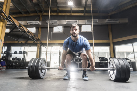 Strong white man deadlifts in crossfit box Stock Photo