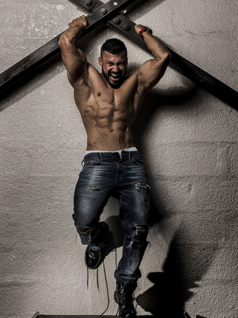 Muscular Man shirtless Holding to steel bars on the Wall Stock Photo