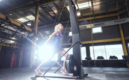 muscle toning: beautiful blonde girl on Crossfit Ski machine