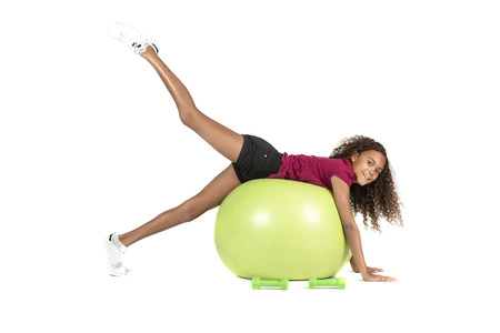 Young playful child or Pre teen biracial girl with brown curly hair playing or exercising on a large rubber ball