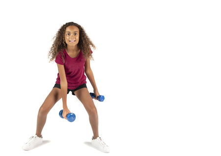 Young playful child or Pre teen biracial girl with brown curly hair exercising with small blue dumbbells