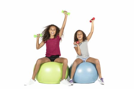 Two young playful children or pre teen biracial girls with brown curly hair playing or exercising on large rubber balls lifting dumbbells Stock Photo