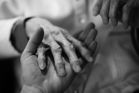 Young man s hand holding seniors hand