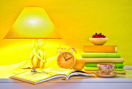 Lamp, books, hours, cup of tea, plate of cherry. photo