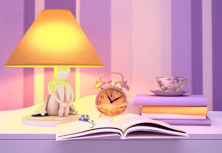 Lamp, books, hours, cup of tea. photo