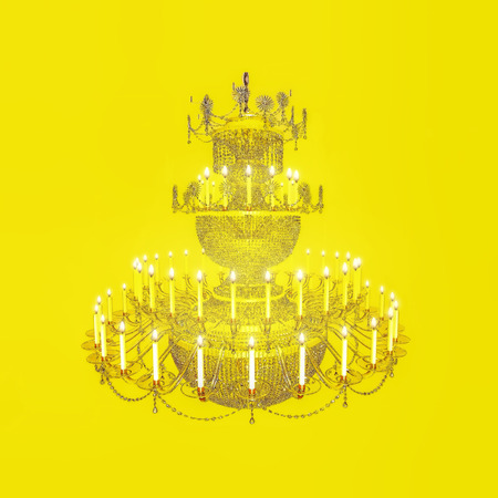 chandelier background: Three-level crystal chandelier with the burning candles on a yellow background. Chandelier, crystal, candles, celebration. Stock Photo