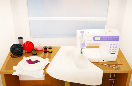 diagonal: Still life with a sewing machine, embroidery, details and cloth. Stock Photo