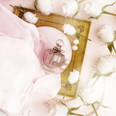 Perfume bottle, roses and pearls located on the folds of pink silk.