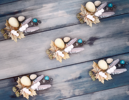 Bird feathers, stones, eggs, oak leaves, acorns, maple leaves on wooden background on top view.