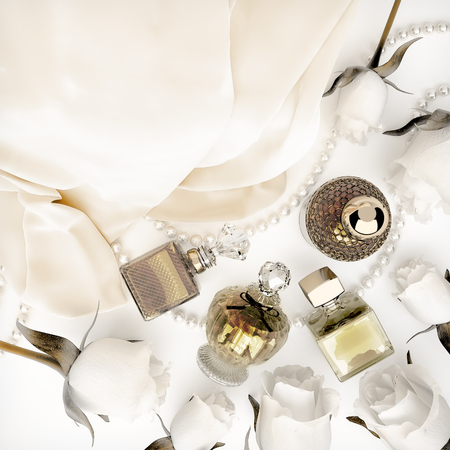 Perfume bottles, roses and pearls located on the folds of white silk.